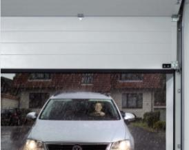 Picture of car driving into garage, under remotely operated garage door in wet weather